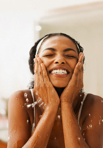 A lady washing her face